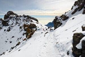 Guiden vækker dig kl. 23:30 (dag 06) og byder på te og lidt snacks, inden vi bevæger os op mod toppen.   På vej mod Hans Meyer Cave er stien meget stenet. Når vi når Hans Meyer Cave, fortsætter vi mod Gillman's point. Vi befinder os nu i en højde af 5681 meter.  At nå til dette punkt er en enorm præstation, da vejen både er stejl og stenet.  Gillman's point ligger i kraterranden, og herfra vil du ofte opleve, at stien mod toppen, Uhuru Peak, er dækket af sne.   Vi ankommer til Uhuru Peak – toppen af Kilimanjaro og 5895 meter i højden.  Du får tid til at tage nogle billeder og nyde en kop te, inden vi bevæger og nedad mod Horombi Hut igen.   Vi starter med at gå til Kibo Hut, hvilket tager ca. 3 timer.   Her hviler vi og nyder en frokost, inden vi bevæger os til Horombu Hut, hvor vi spiser aftensmad, vasker os og overnatter.